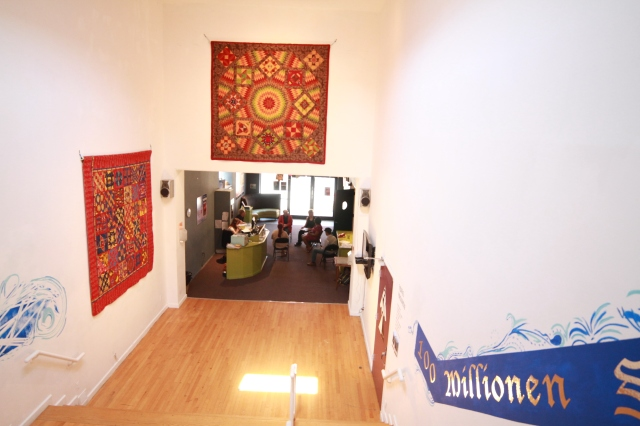 "Gallery with quilts of Sarah Bond in view. The center quilt facing the viewer ""India Broken Star"" quilt."
